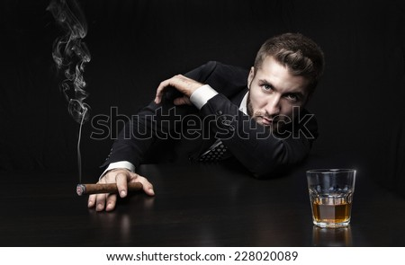 Attractive man with a cigar and a whiskey - stock photo