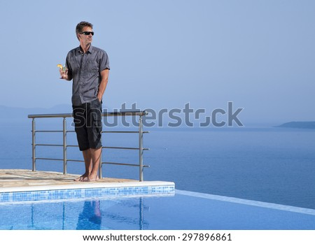 Attractive man with a cocktail on an infinity pool - stock photo