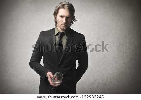 attractive man with a glass of wine on gray background - stock photo