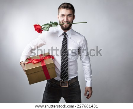 Attractive man with a present in his hand and a rose in his mouth - stock photo