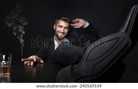 Attractive man with cigar and a glass whiskey - stock photo