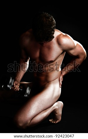 Attractive Man with Dumbbell Hand Weights Nude Over Black Background - stock photo