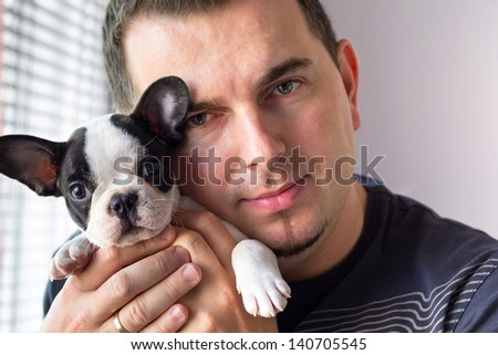 Attractive man with french bulldog puppy - stock photo