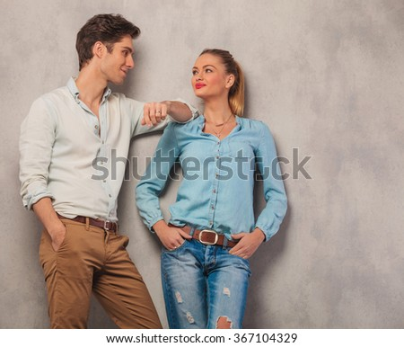 attractive man with hand in pocket lean on girl shoulder while she looks at him with hands in pockets in studio background - stock photo