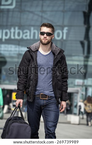 Attractive man with sunglasses and a suit case - stock photo