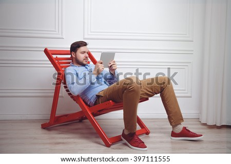 Attractive man working on tablet pc on the chaise-longue - stock photo