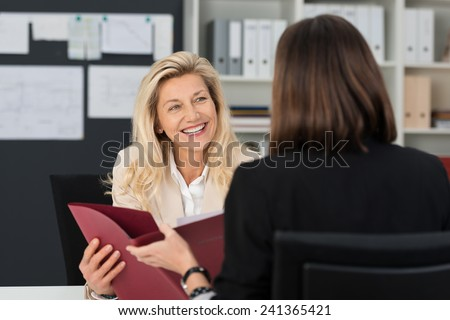Attractive manageress conducting a job interview with a female applicant smiling at her as they discuss her CV