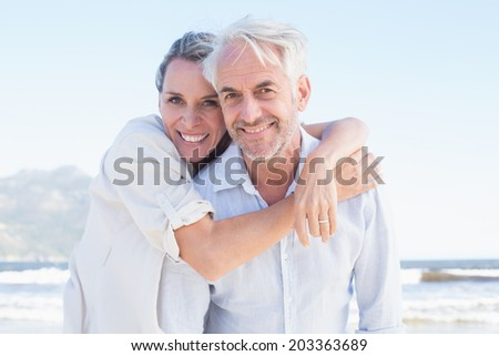 Attractive married couple posing at the beach on a sunny day - stock photo