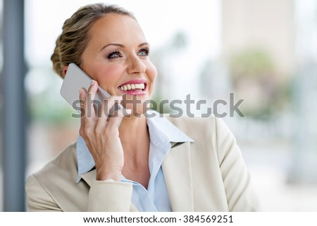 attractive mature business executive talking on mobile phone - stock photo