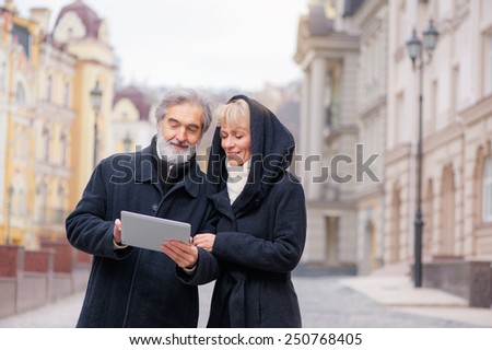Attractive mature caucasian couple standing in urban street reading information on a tablet computer with a smile - stock photo