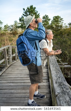 Attractive mature couple hiking and birdwatching on old wooden footbridge in Florida wetlands.