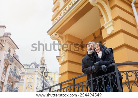 Attractive mature couple walking in the old part of town - active retirement concept - stock photo