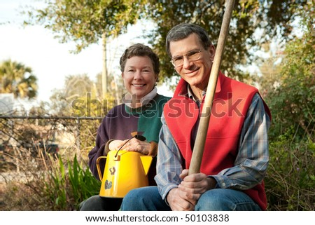 Attractive mature couple with gardening implements in their spring garden. - stock photo