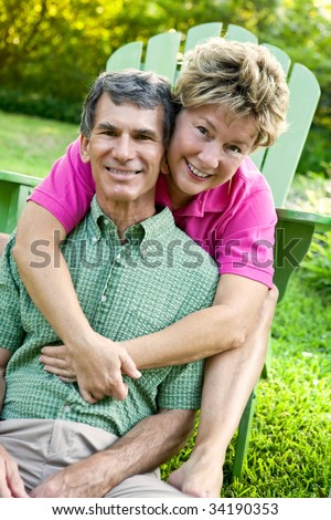 Attractive mature man and woman hugging and happy in their backyard