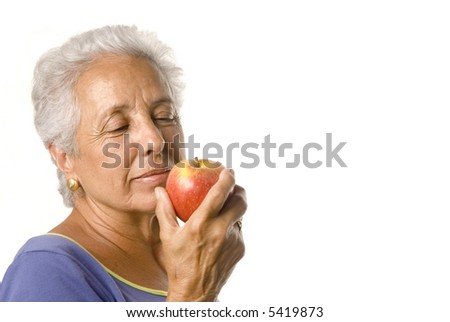 Attractive mature woman eating a red apple