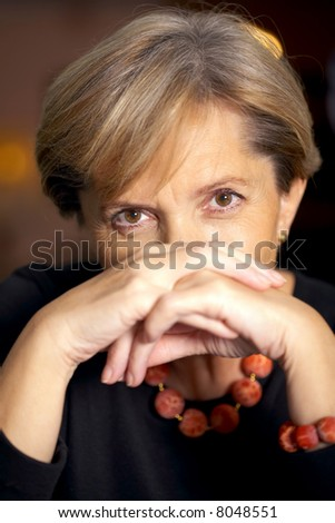 Attractive mature woman leaning on hands - stock photo