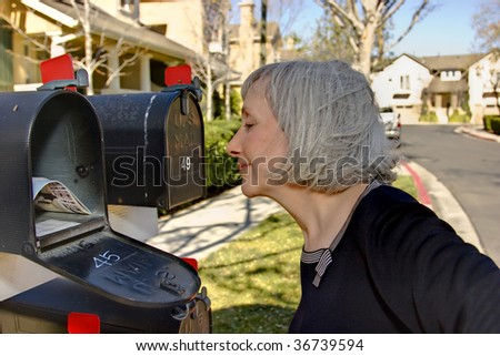 Attractive mature woman looking into her mailbox - stock photo