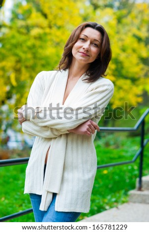 attractive mature woman outside in the park thinking - stock photo