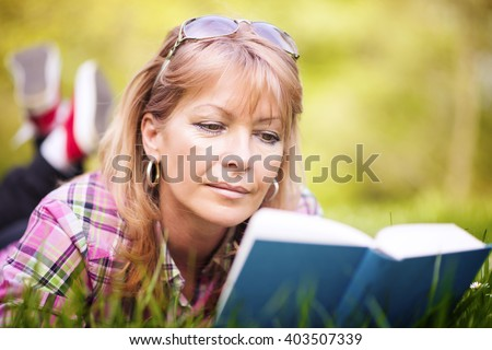 Attractive mature woman reading a book in the park.Moment of leisure. - stock photo