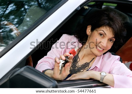 Attractive mature woman sitting in the car and  holding a car key - stock photo