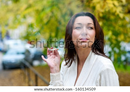 attractive mature woman smoking cigarette in the park - stock photo
