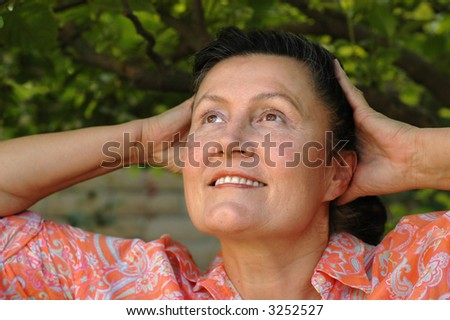 Attractive mature woman stretching in her garden - stock photo
