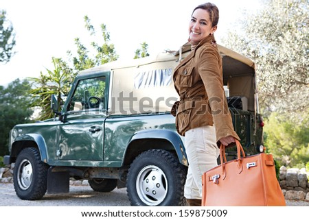 Attractive mature woman tourist getting ready for adventure while visiting a safari park on vacation with a four wheel drive car, turning to camera smiling during a sunny day outdoors.