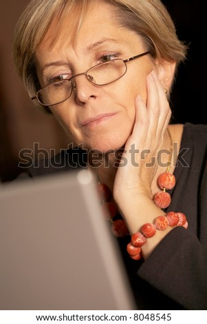 Attractive mature woman using laptop - stock photo