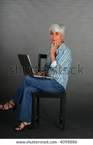 attractive mature woman working on laptop sitting on a chair - stock photo