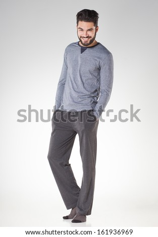 attractive men in pyjamas smiling isolated on grey - studio - stock photo