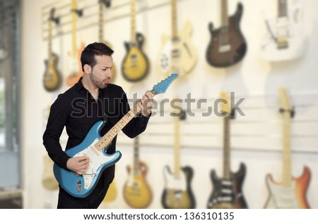 Attractive men playing a electric guitar in a music store - stock photo