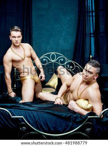 attractive men wearing golden chain and underwear in bed with black linen