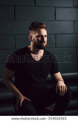 attractive men with beard in black shirt having problems in his life near brick wall