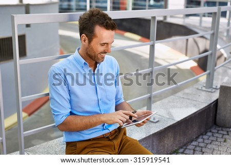 Attractive mid adult man sitting with digital tablet outside the office - stock photo