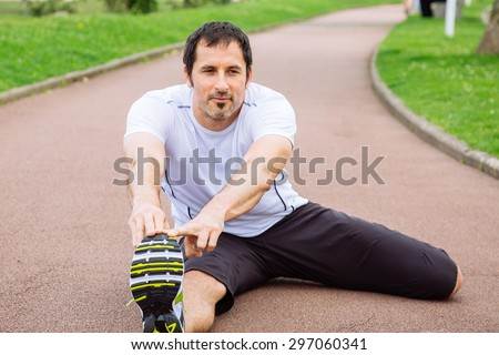 Attractive mid adult spotrsman doing stretching exercises outdoors in a track - stock photo