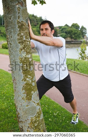 Attractive mid adult spotrsman doing stretching exercises outdoors using a tree - stock photo