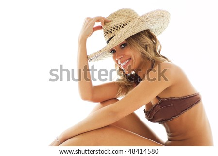 attractive mid adult woman in swim wear, holding straw hat and looking at camera on white background. Horizontal shape, copy space - stock photo