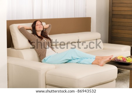 Attractive mid-aged woman relax modern living room on leather sofa - stock photo