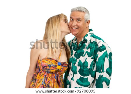 Attractive middle age couple in a affectionate pose with colorful clothes on a white background.