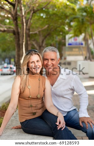 Attractive middle age couple posing in a downtown scene with street and trees in the background. - stock photo