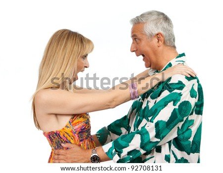 Attractive middle age couple with a funny expression and colorful clothes on a white background.
