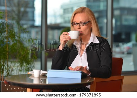 Attractive middle-aged blond businesswoman working at hotel lobby with a tablet pc and drinking coffee - stock photo