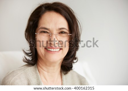 Attractive middle-aged brunette woman with a beautiful smile sitting against apartments background looking directly at the camera. Close up portrait of a senior middle aged lady relaxing at home. - stock photo