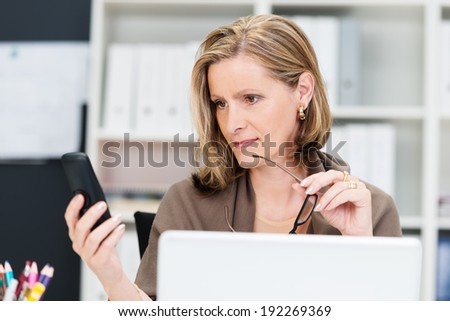 Attractive middle-aged businesswoman pausing in her work with her glasses in her hand to read a text message on her mobile phone - stock photo