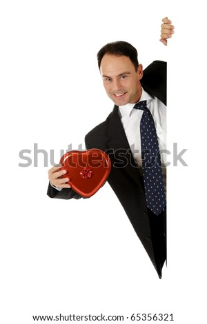 Attractive middle aged caucasian businessman behind a wall showing box of valentine chocolates, heart shaped. Copy space. Studio shot. White background. - stock photo