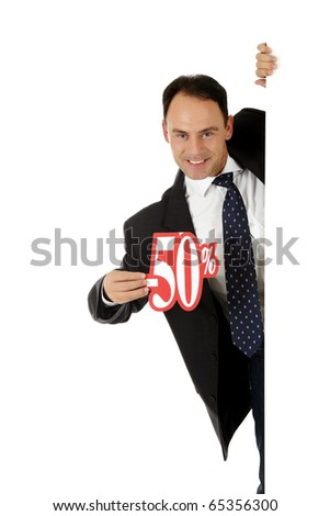Attractive middle aged caucasian businessman behind a wall showing fifty percent discount sign. Copy space. Studio shot. White background.