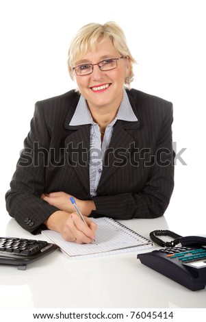 Attractive middle aged caucasian businesswoman in office with telephone and keyboard on her desk, writing on a notebook. Studio shot. White background. - stock photo
