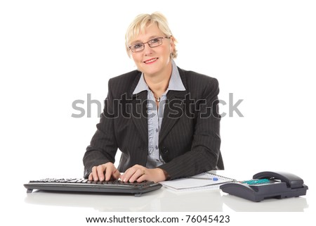 Attractive middle aged caucasian businesswoman in office with telephone and notebook, typing on keyboard. Studio shot. White background. - stock photo