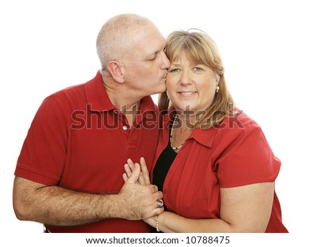Attractive middle-aged couple in love.  He's kissing her on the cheek.  Isolated on white. - stock photo