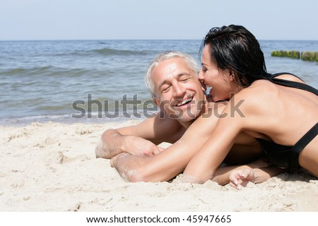 Attractive middle aged couple relaxing on the beach - stock photo